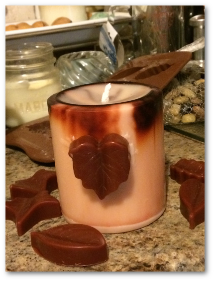 Putting the fall leaf onto the soy pillar candle